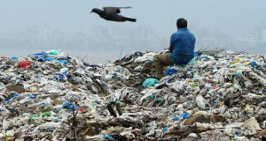 A man sits on a mountain of plastic garbage in Mumbai: India has pledged to eliminate disposable plastics within three years. (Photo by Akira Kodaka)