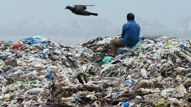 A man sits on a mountain of plastic garbage in Mumbai: India has pledged to eliminate disposable plastics within three years. (Photo by Akira Kodaka)
